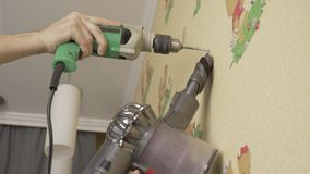 Adult caucasian man drilling the wall at home with electric drill. Close up locked down shot. Low angle. Diy man use. Vacuum cleaner. DIY stock video
