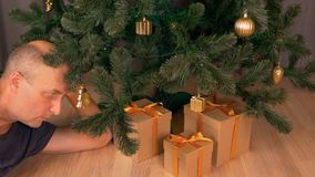Adult caucasian man put gift box under christmas tree. Christmas eve night celebrate holiday. Christmas tree in living. Room. Gold decor golden bow on brown stock video footage