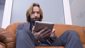 Adult caucasian man sits on sofa and uses digital tablet. Handsome man uses his tablet sitting on sofa. The businessman wearing suit is relaxing and looking the stock footage