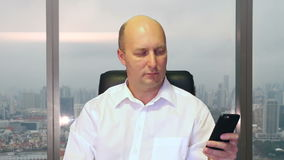 Adult caucasian man texting on smartphone sitting on chair in office window behind his. Dolly shot. Adult caucasian man texting on smartphone sitting on chair stock video