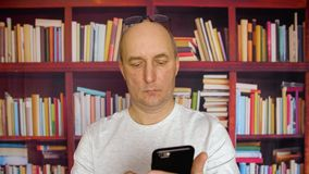 Adult caucasian white man use smart phone at bookshelf background home library