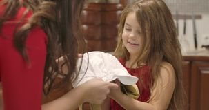 Adult Caucasian woman giving little girl apron and cook hat. Joyful child smiling and looking at her mother. Happy kid stock footage