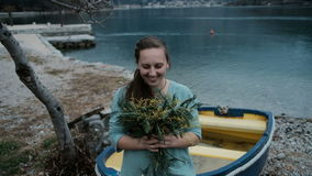 Adult Caucasian woman is happy receive bouquet of mimosa near lake. Young fair-haired lady with hairstyle based on tress fixed by white scrunchy in blue dress stock footage