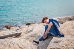 Adult caucasian women sit on rocky beach with blue neckchief relaxing and thinking about something. Adult caucasian woman sit on rocky beach with blue neckchief royalty free stock photos
