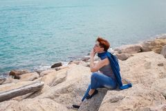 Adult caucasian women sit on rocky beach with blue neckchief relaxing and thinking about something. Adult caucasian woman on rocky beach with blue neckchief royalty free stock photography