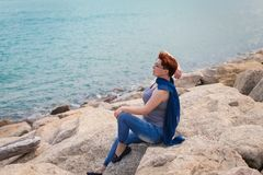 Adult caucasian women sit on rocky beach with blue neckchief relaxing and thinking about something. Adult caucasian woman sit on rocky beach with blue neckchief stock image