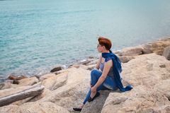 Adult caucasian women sit on rocky beach with blue neckchief relaxing and thinking about something. Adult caucasian woman sit on rocky beach with blue neckchief royalty free stock photography