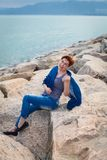 Adult caucasian women sit on rocky beach with blue neckchief relaxing and thinking about something. Adult caucasian woman sit on rocky beach with blue neckchief stock photo