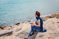 Adult caucasian women sit on rocky beach with blue neckchief relaxing and thinking about something. Adult caucasian woman sit on rocky beach with blue neckchief stock photos