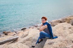 Adult caucasian women sitting on rocky beach with blue neckchief relaxing and thinking about something. Adult caucasian woman sitting on rocky beach with blue royalty free stock images