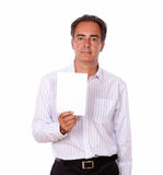 Adult charismatic male holding a white card. Portrait of an adult charismatic male holding a white blank card while standing on isolated background - copyspace Stock Photos