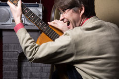 Adult cheerful man with acoustic guitar Stock Image