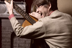 Adult cheerful man with acoustic guitar. Stock Photography