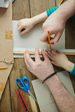 Adult and child drawing together. Little child and his male teacher working together on creation of toy plane sketch with ruler and pencil, high angle view Royalty Free Stock Photos