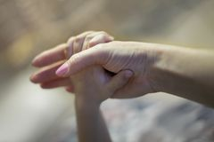 Adult and child hands together. Adult caucasian woman arm holds little child hand on blurred background. Local focus, care and ten stock photo
