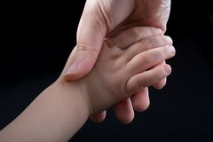 Adult and child hold hands. In black background Royalty Free Stock Images