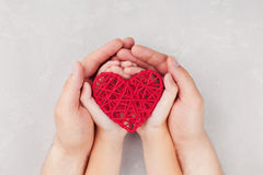 Adult and child holding red heart in hands top view. Family relationships, health care, pediatric cardiology concept.