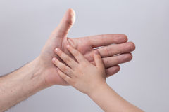 Adult and child's hand touching help tenderness Stock Photography