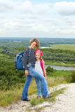 Adult and child standing on a mountaintop near  river. Royalty Free Stock Photos
