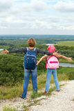 Adult and child standing on a mountaintop near  river. Royalty Free Stock Images