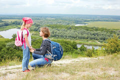Adult and child standing on a mountaintop near  river. Family hiking in mountains on vacation Royalty Free Stock Image
