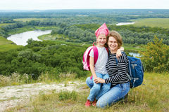 Adult and child standing on a mountaintop near  river. Stock Photo