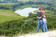 Adult and child standing on a mountaintop near  river. Mother with little daughter hiking in mountains on vacation Royalty Free Stock Photos