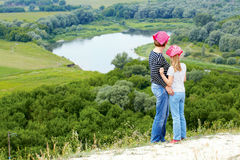 Adult and child standing on a mountaintop near  river. Stock Images