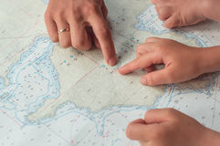 Adult and children`s hands on the map Stock Photography