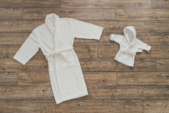 Adult and children`s white robes lying on wooden background. Adult and children`s white robes lying on the wooden background and are drawn to each other Stock Images