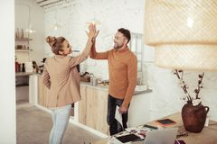Adult colleagues smiling and high-fiving each other. Friendly atmosphere. Two happy colleagues smiling and high-fiving each other standing in the kitchen royalty free stock photo