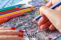 Adult coloring books. On blue table stock photos