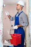 Adult concentrated man repairer working with roller in uniform, Stock Photography