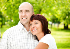 Adult couple. Of husband and wife in park, both smiling and looking away from camera stock photo