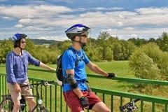 Adult couple on bikes stopping on a bridge. DOBERSBERG, AUSTRIA - AUGUST 2016: Adult couple on bikes stopping on a bridge to enjoy the view. Photo was taken next royalty free stock image