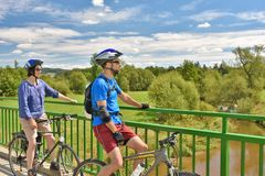 Adult couple on bikes stopping on a bridge. DOBERSBERG, AUSTRIA - AUGUST 2016: Adult couple on bikes stopping on a bridge to enjoy the view. Photo was taken next royalty free stock photos