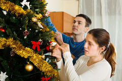 Adult couple decorating room. Adult couple decorating Christmas tree in home interior royalty free stock photo