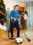 Adult couple doing housework. Adult couple cleaning with vacuum cleaner in living room royalty free stock photography
