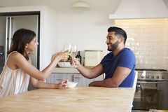 Adult couple drinking wine make a toast in the kitchen Royalty Free Stock Photos