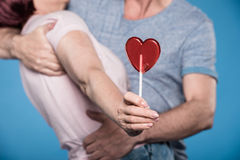 Adult couple embracing and holding lollipop in form of heart. Cropped shot of adult couple embracing and holding lollipop in form of heart stock photo