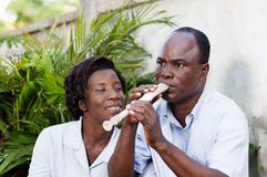 Adult couple entertaining themseve in  campaign. Adult women watching her husband play the flute, smiling Stock Image