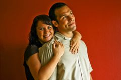 Adult Couple Hugging in Love. Young adult couple hugging and in love, against a red background stock images