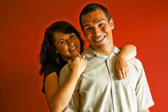 Adult Couple Hugging in Love Smiling. Young adult couple hugging and in love, against a red background Royalty Free Stock Image