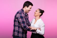 Adult couple looking at eatch other and smiling. On pink background in studio stock photo