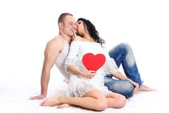 Adult couple with red heart. Happy young adult couple with red heart on the floor, embracing and laughing stock images