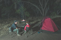 Adult couple relaxing in camping site by night. Adventure in National Park, South Africa. Burning camp fire and tent in the backgr Stock Image