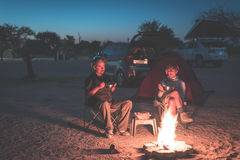 Adult couple relaxing in camping site by night. Adventure in National Park, South Africa. Burning camp fire and tent in the backgr Royalty Free Stock Photography