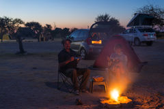 Adult couple relaxing in camping site by night. Adventure in National Park, South Africa. Burning camp fire and tent in the backgr Royalty Free Stock Image