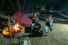 Adult couple relaxing in camping site by night. Adventure in National Park, South Africa. Burning camp fire and tent in the backgr Stock Photos