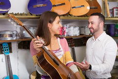 Adult couple selecting acoustic guitar in shop Stock Image